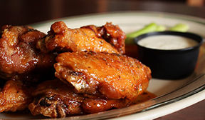 Close up view of saucey chicken wings with ranch dressing in background.