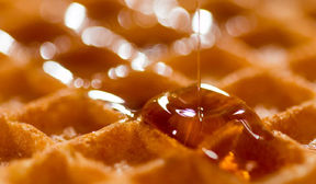 Close up of a few waffle squares with syrup pouring carefully and overflowing one square.