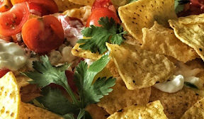 Plate of nachos with parsley tomatos and toppings.