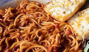 Close up view of spaghetti with meat sauce and cheese bread.